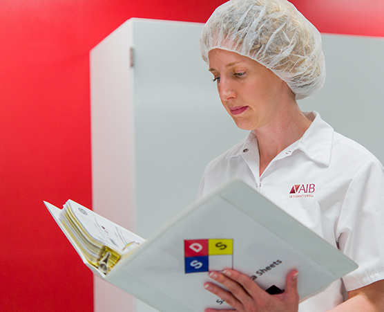 Woman in food facility filling out clipboard