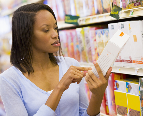 Woman inspecting a cereal box nutrition label