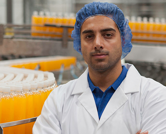 A man wearing a hair net with bottles on the production line behind him