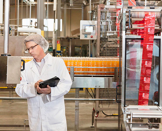 A man writing on a clipboard and looking through window into manufacturing facility
