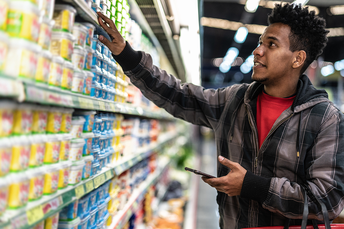 Man looking at food label while holding a cell phone