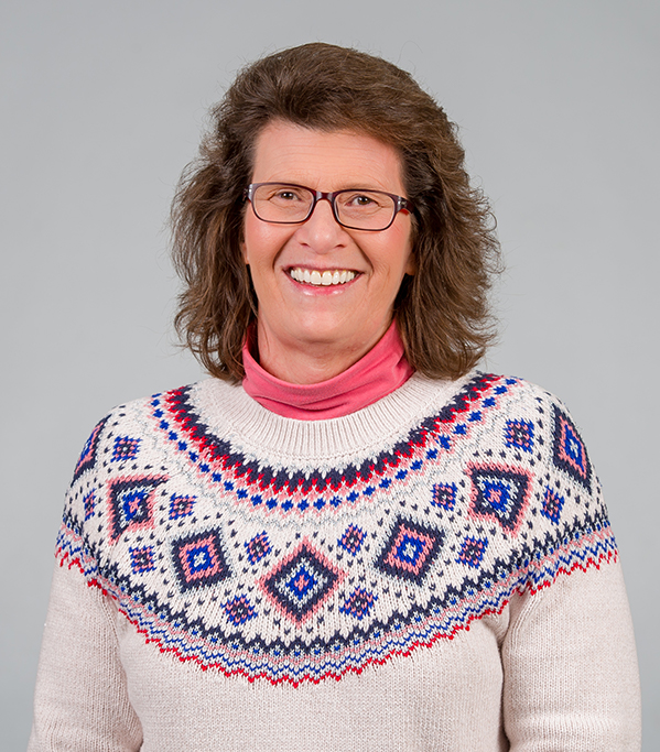 Elain Meloan smiling in front of a grey backdrop wearing a sweater and glasses