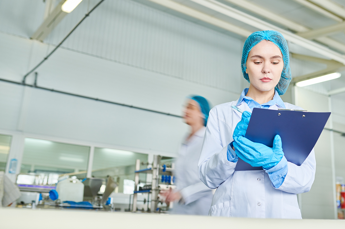 Woman wearing a hair net holding a clipboard