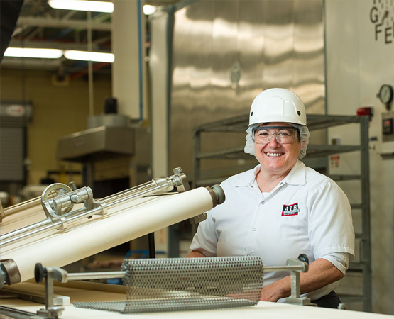 Woman in food manufacturing facility wearing hair net and smiling